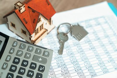 A tiny model of a house, a calculator, a house key, all sitting on a printed spreadsheet.