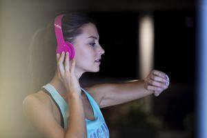 Woman listening to music in headphone via apple watch