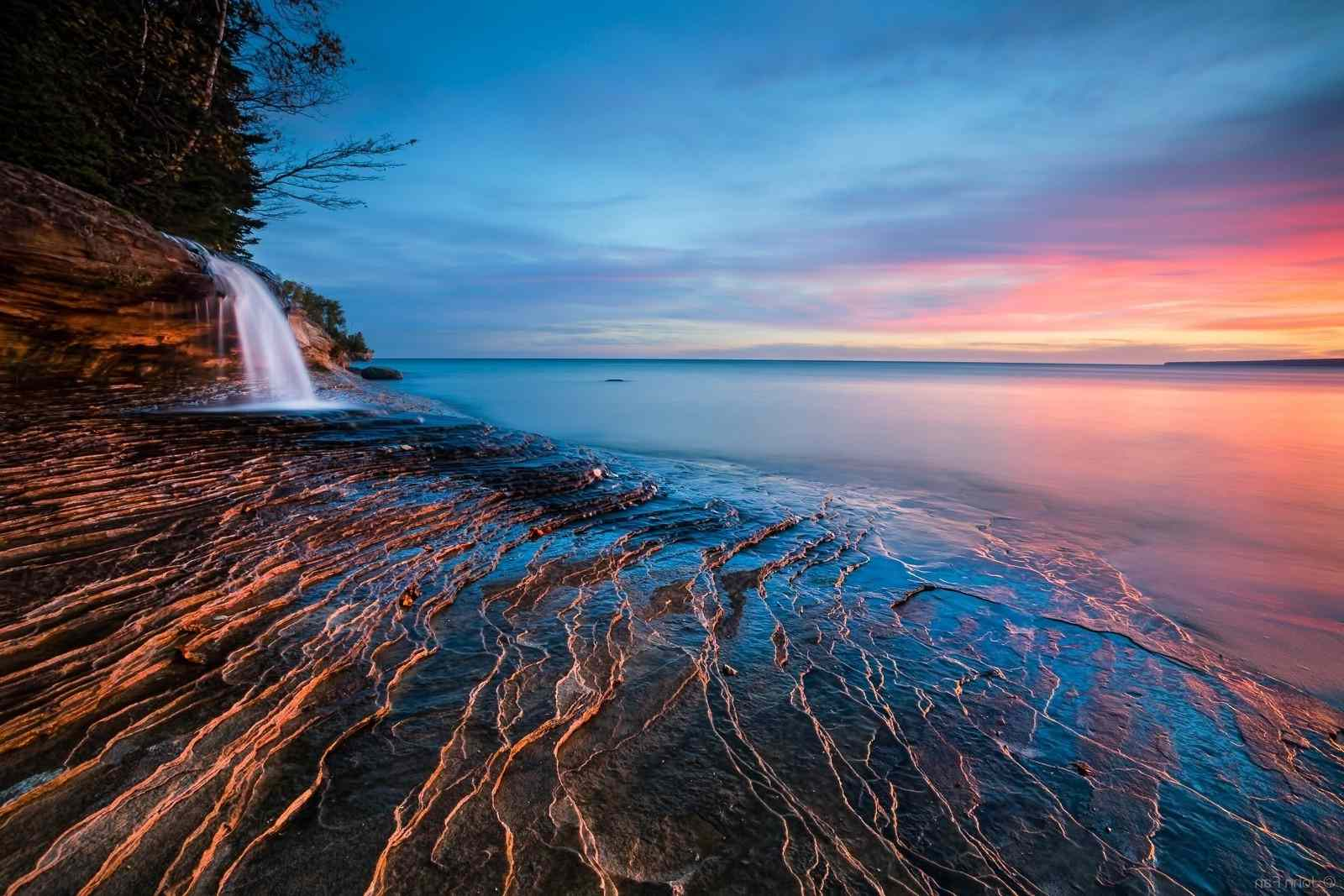 A small waterfall on a beach at sunset in this free ocean wallpaper