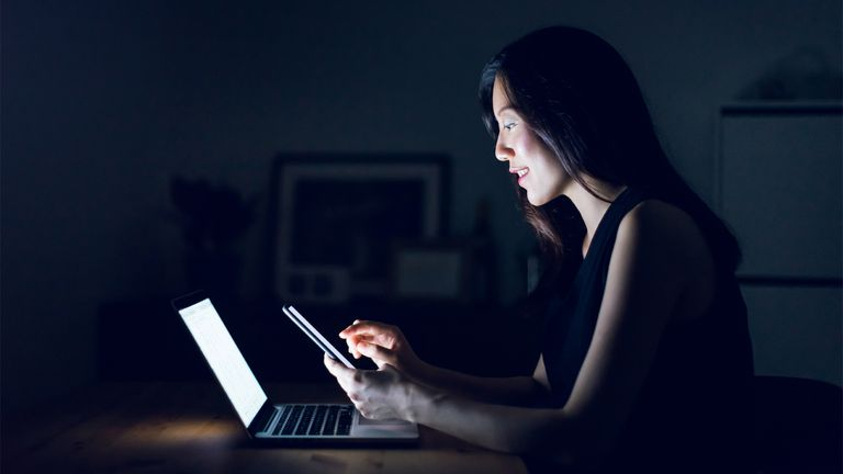 A woman turning on th YouTube Dark Theme on your laptop and smartphone.