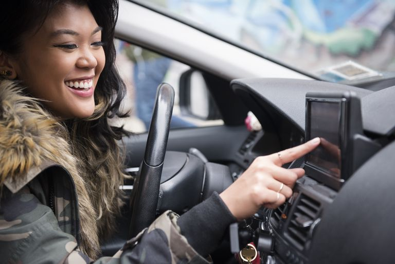 Woman driving car pressing touch screen