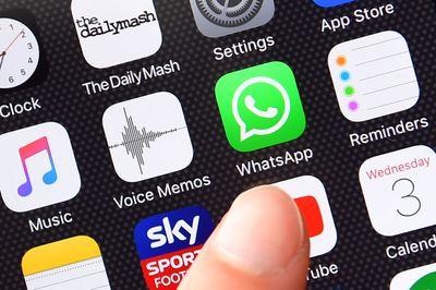 Up close shot of finger next to WhatsApp logo on iPhone screen