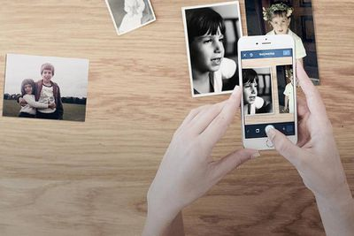 A hand holding a smartphone, using the Photomyne app to scan in several photographs