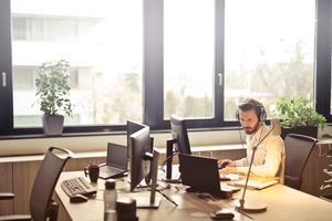 Remote worker wearing headset using computer