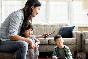 A parent installing a hidden security camera app on a smartphone to look after two children.