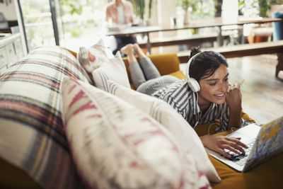 Woman laying on couch listening to music through headphones from computer