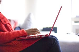 Woman using red laptop
