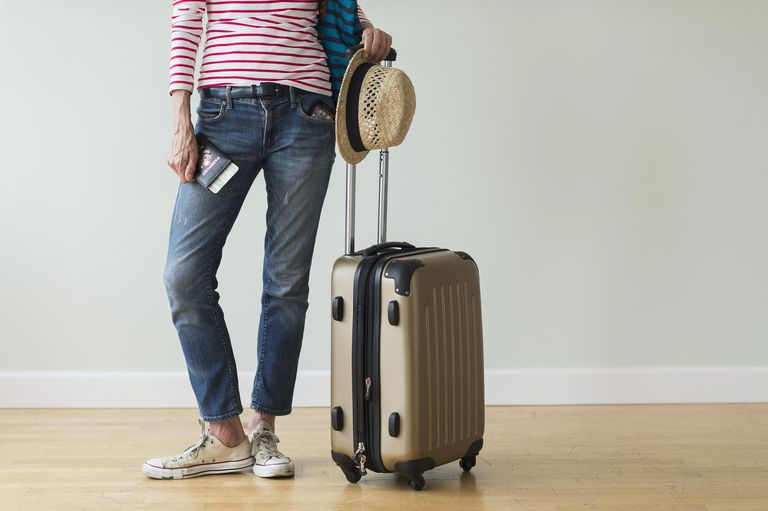 Traveler standing next to suitcase, packed for vacation