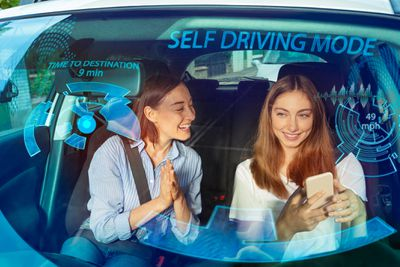 View through the windshield of two people in a car with self driving mode activated and info displayed on the windshield.