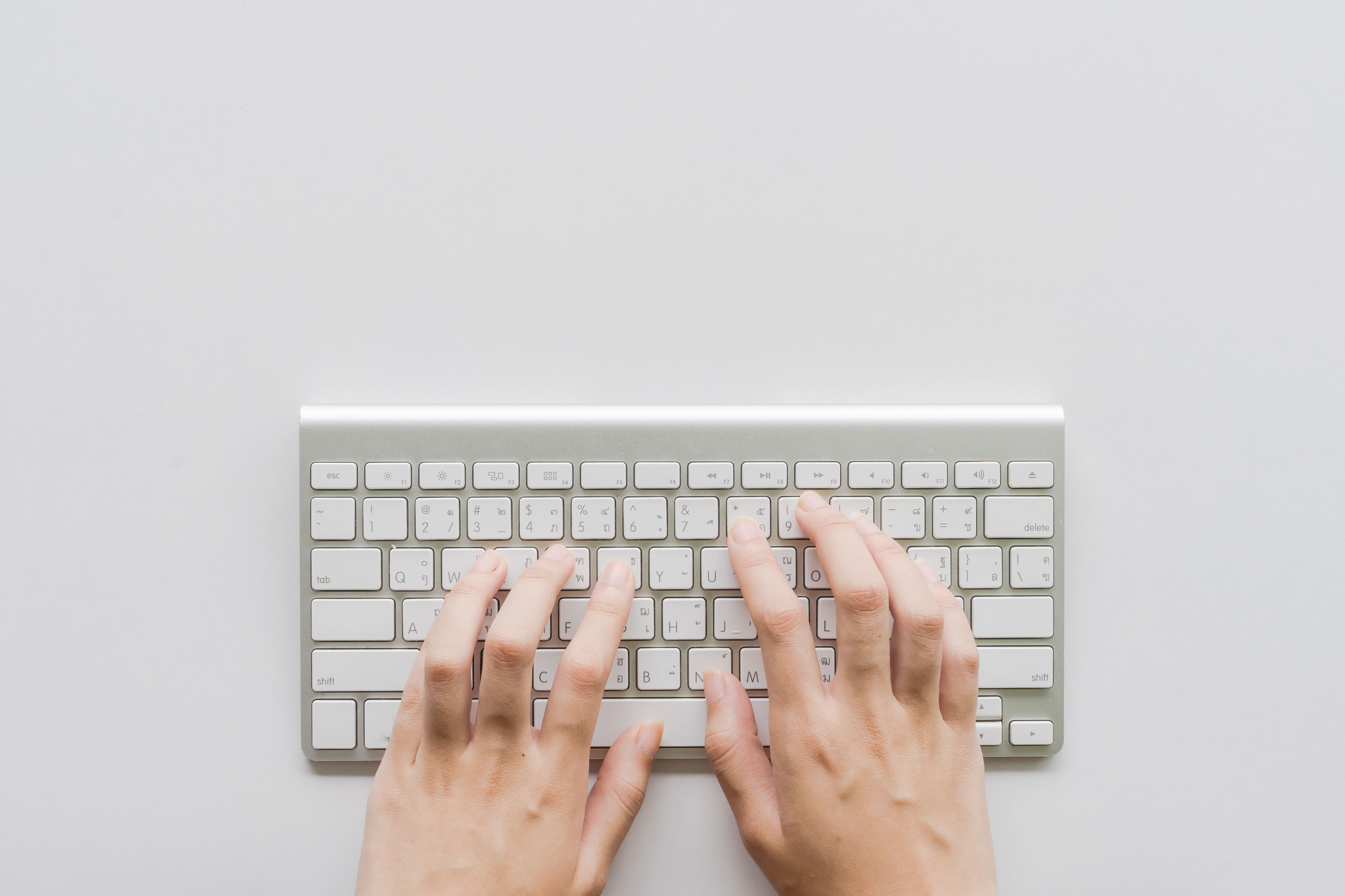 Directly Above Shot Of Person Hands Typing On small Computer Keyboard