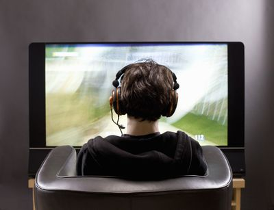 A teenager sits in front of a TV screen playing a game with headphones on