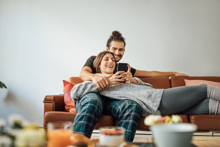 Young couple with smart phone relaxing on sofa.