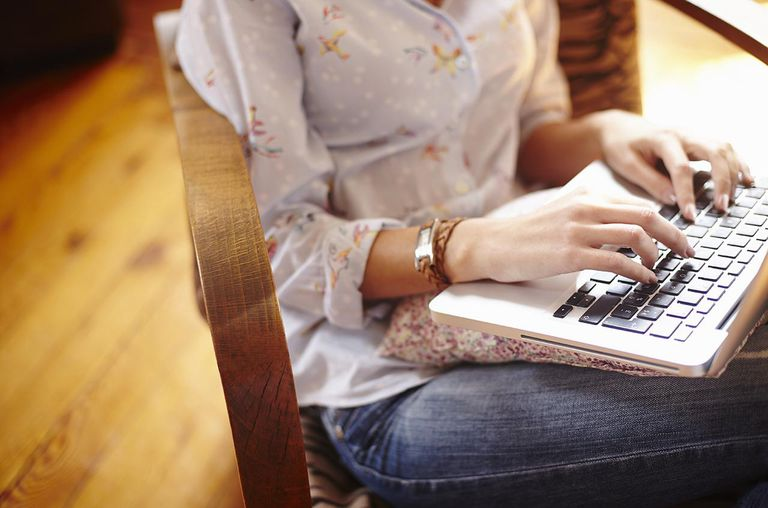 Young woman at home working on laptop