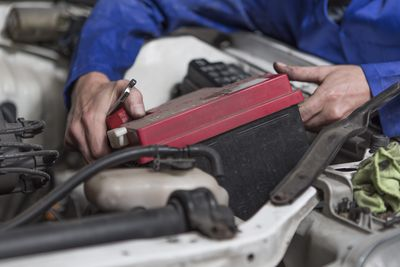 Mechanic working on car removing battery