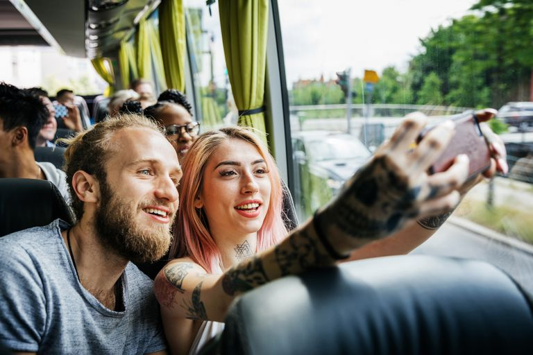 Young couple on a bus taking selfies together.