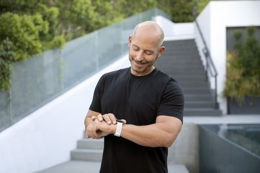 A man looking at the Fitbit Versa 2 watch on his arm.