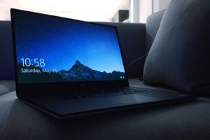 A Dell laptop with what appears to be a Windows 10 lock screen. The laptop is sitting on a couch.