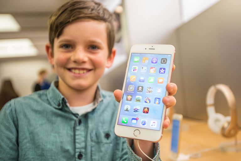Young child holding iPhone 6 Plus at an Apple Store