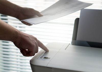 Someone holding papers and pressing a button on a printer.