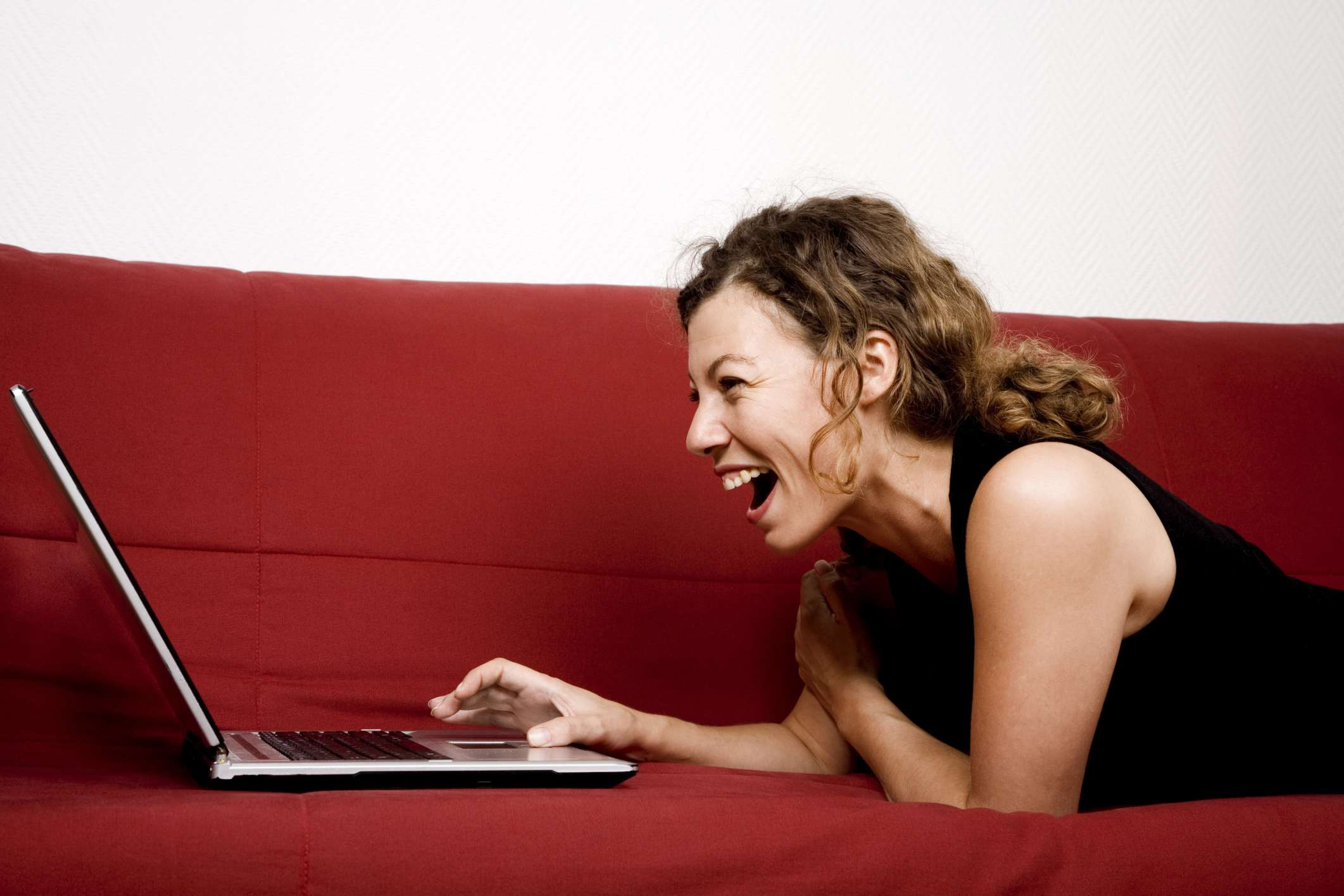 Woman lying on couch looking at computer laughing