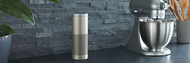 An Amazon Echo Plus sitting on a kitchen counter, waiting for a command.