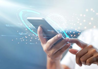 A man holding a smartphone in his hands with CGI rendering of network settings being reset hovering on top of it.