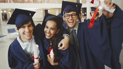 Three happy graduates in caps and gowns with diplomas