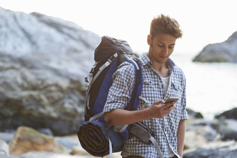 Hiker using mobile phone on rocky beach