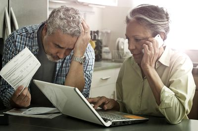 Elderly couple with a laptop, mobile phone, and phone bills.