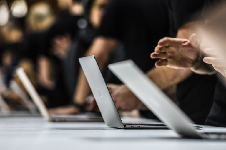 Line up of Macbooks with people's hands above