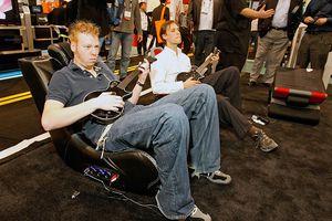 Two guys sitting in gaming chairs playing Guitar Hero