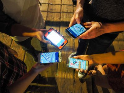 Four people looking at their smartphones playing mobile games