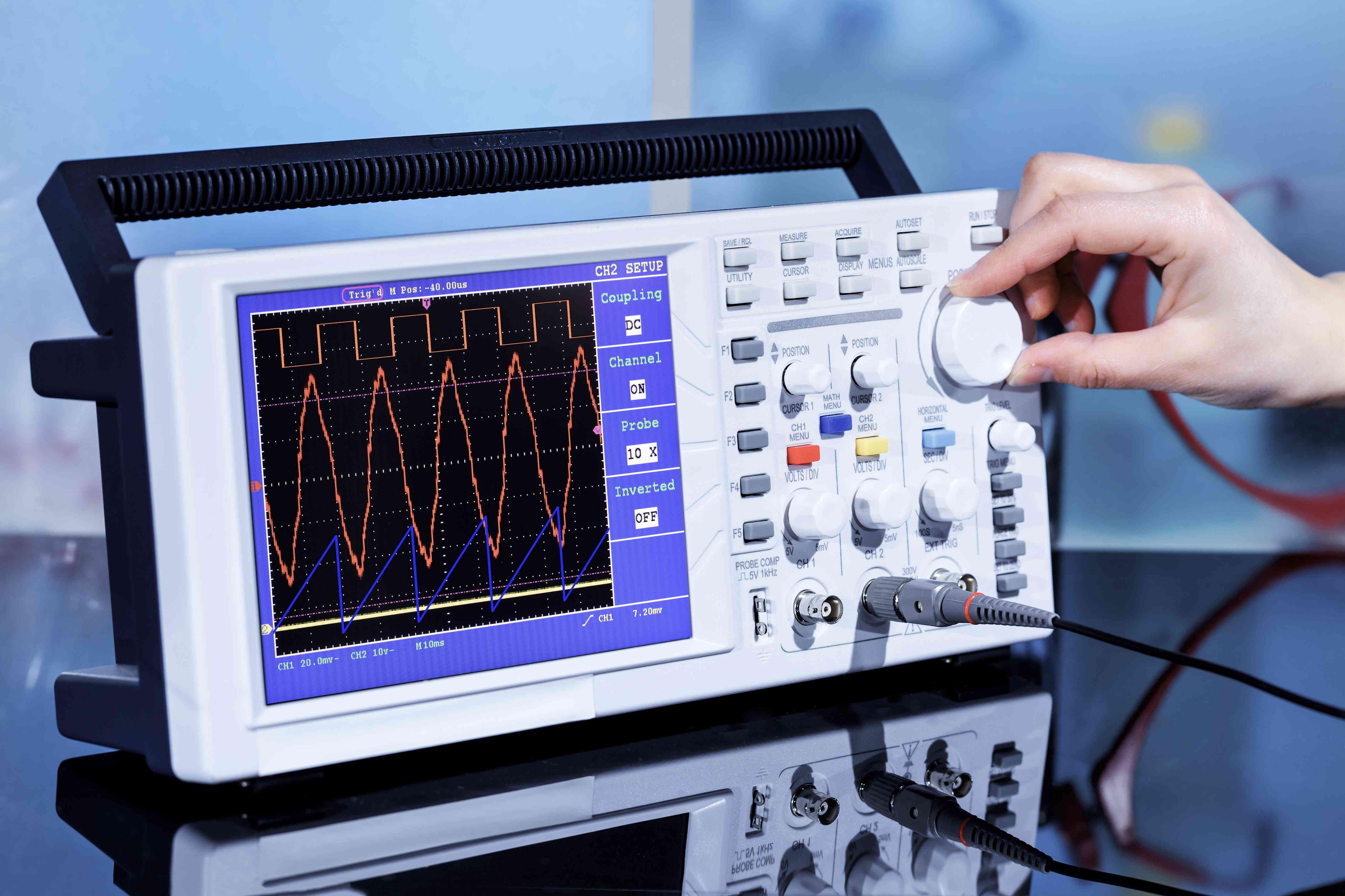 Hand adjusting dial on oscilloscope