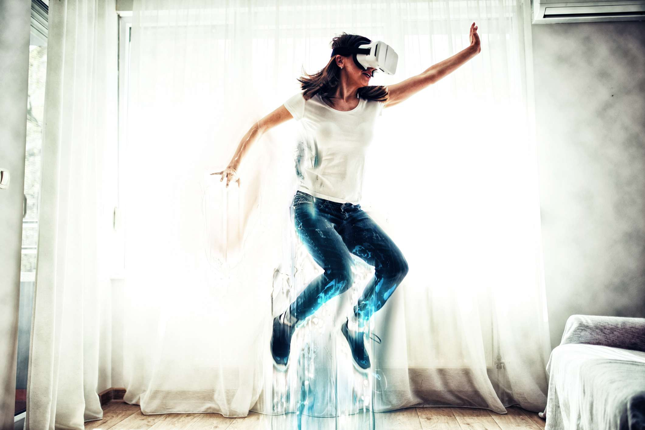 Woman jumping into the air while playing a VR game.