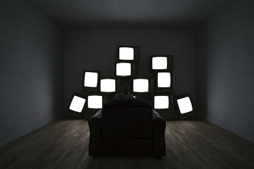 Someone sitting in a dark room in front of multiple TV sets showing solid white screens.