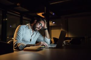 A man sitting in the dark at a desk looking at a laptop