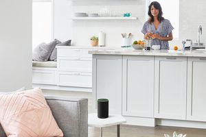 Homeowner in kitchen looking at Amazon's Echo