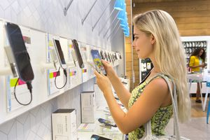 Young woman browsing smartphones in phone store
