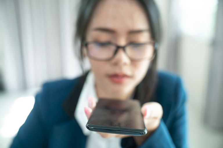 A woman looking at an iPhone placed flat on her palm