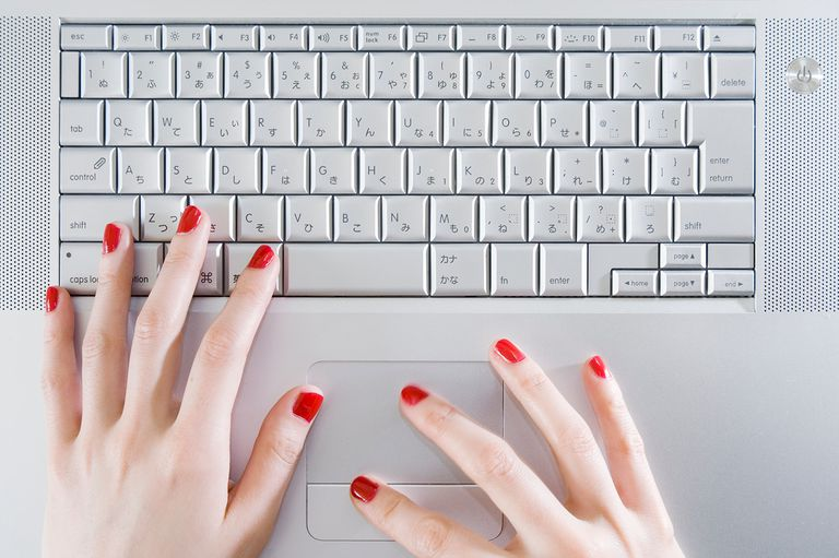 Woman wearing red nail polish using laptop, close-up of hands, overhead view