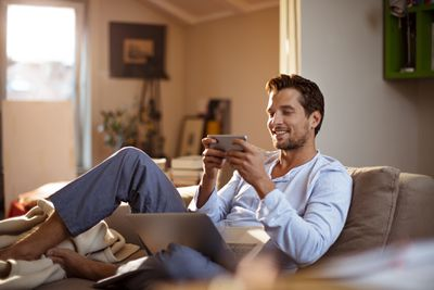 A man sitting on a couch playing a game on an iPhone and smiling at it