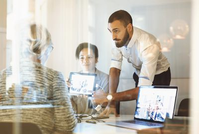 Business people giving presentation to colleague in office