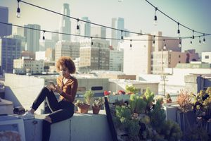 A woman sitting on a balcony rooftop looking at her smartphone