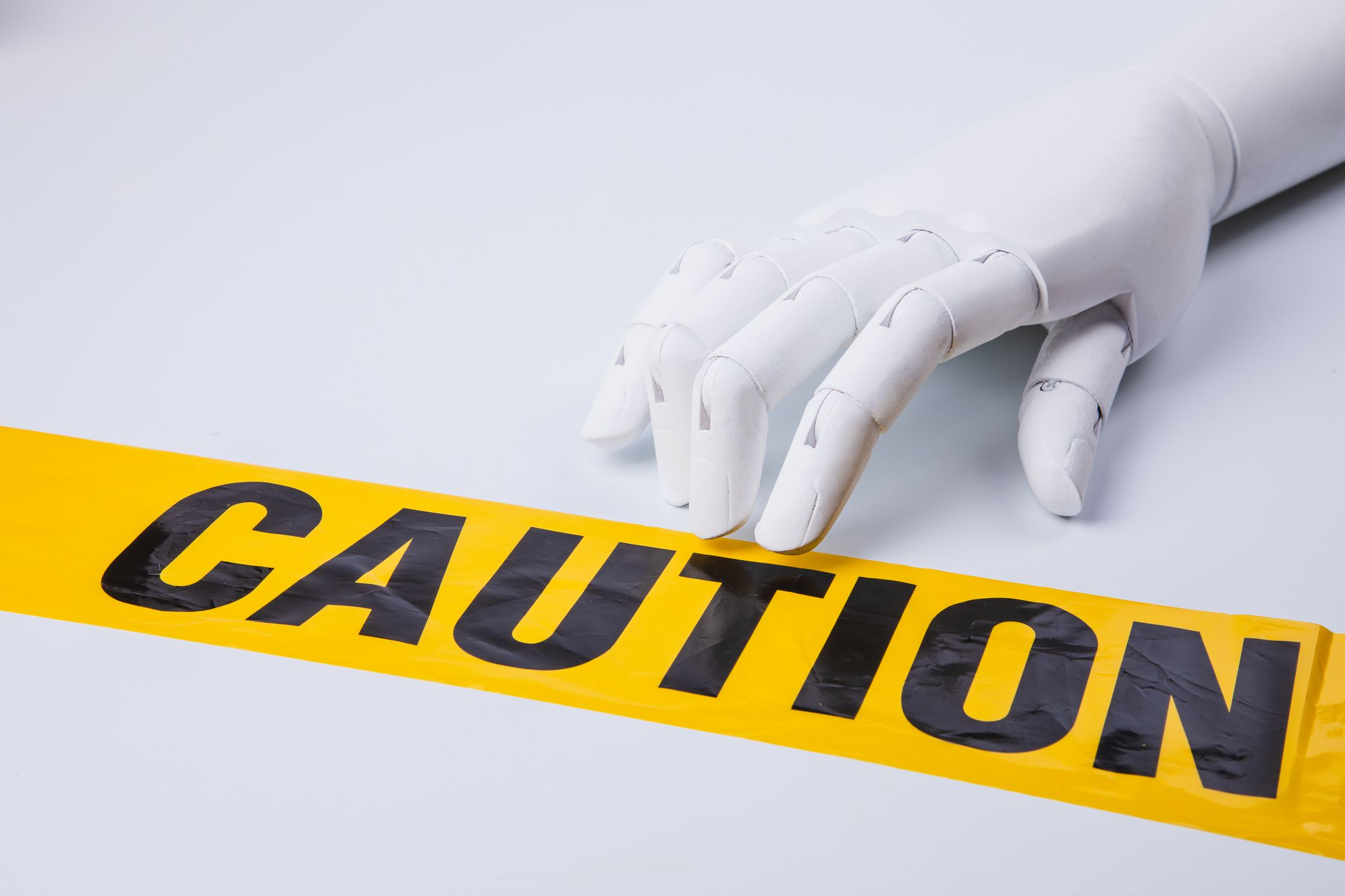 A white robot hand touching a piece of caution tape against a white background.