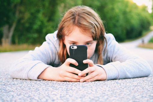 Girl using her mobile phone to take pictures.
