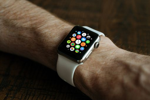 Apple Watch on a wrist, showing the home screen app grid