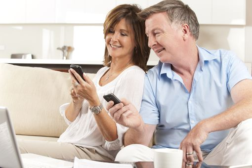 Woman and man in their 40s sitting on a couch and using dating apps and websites on their smartphones and laptop.