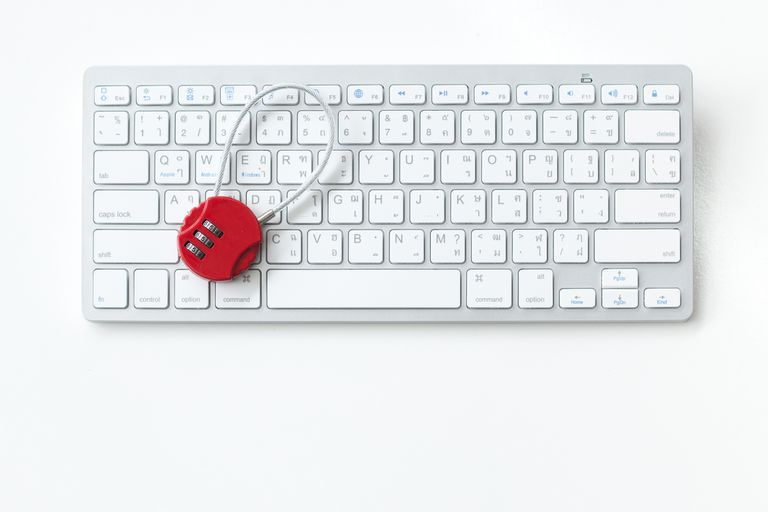 A dial lock on top of a white keyboard