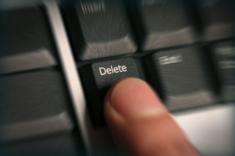 Finger on Delete button on a keyboard