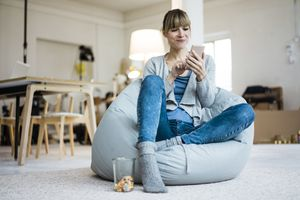 Woman sitting on beanbag reading her iPhone and smiling